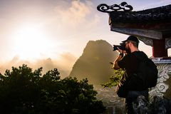 Fotograaf die zonsopgang over karst rotsen in Yangshuo-Kin vangen Royalty-vrije Stock Afbeelding