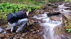 Fotograaf met camera op driepoot Stock Foto's