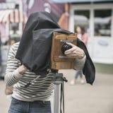 Fotograaf met uitstekende houten camera onder donkere doekkaap, die cliënten, artefact, antiquiteit fotograferen stock fotografie
