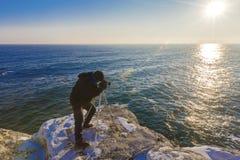 Fotograaf op de rotsen die landschapsbeelden nemen Stock Foto's