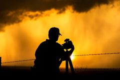 Fotograaf tegen zonsondergang wordt ontworpen die stock foto's