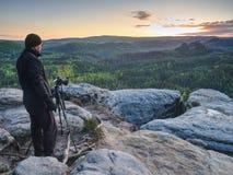 Fotograafreiziger die en om driepoot voor camera te plaatsen denken stock afbeeldingen