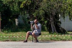 Fotograafzitting op een stoel en het nemen van schoten royalty-vrije stock afbeeldingen