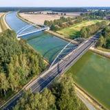 Fotografía aérea de las instalaciones infraestructurales para los coches, trenes y naves, sobrevuelo de un canal con un puente fe Imagen de archivo