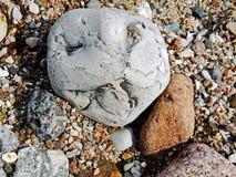 Fotografía abstracta de una cara de piedra de mueca en la playa del thre Imágenes de archivo libres de regalías