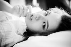 Fotografía blanca negra de la mujer joven hermosa que miente en la cama que toca sus labios Foto de archivo
