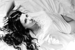 Fotografía blanca negra de la mujer joven hermosa que miente en una cama en pijamas Imagenes de archivo