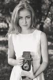 Fotografía blanca negra de la mujer rubia hermosa joven con la cámara retra en fondo de la naturaleza del verano Fotografía de archivo libre de regalías