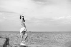Fotografía blanco y negro de la señora joven hermosa que disfruta de la opinión del mar sobre fondo del cielo del agua del aire l Foto de archivo libre de regalías