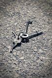 Fotografía blanco y negro de las viejas llaves aherrumbradas que mienten en un camino concreto imagen de archivo libre de regalías