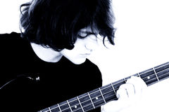 Fotografía común: Muchacho adolescente joven que toca la guitarra baja Imagen de archivo libre de regalías