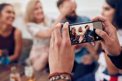 Fotografía de amigos en el partido con el teléfono móvil imagen de archivo