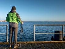 Fotografía de la afición con la cámara en el trípode a disposición Puente del tablero de madera Foto de archivo libre de regalías