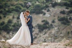 Fotografía de la boda de un par joven, de la novia y del novio en un área montañosa en verano Fotografía de archivo libre de regalías