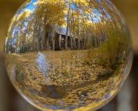 Fotografía de la bola de cristal Cabina en bosque con una corriente imagen de archivo