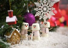 Fotografía de la comida de la Navidad de las melcochas formadas como muñecos de nieve en nieve debajo de un árbol de navidad con  Foto de archivo libre de regalías