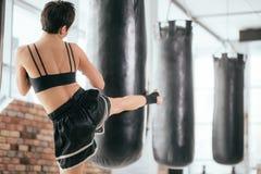 Fotografía de la vista posterior del boxeo de retroceso con el pie del atleta de la mujer joven Imagen de archivo