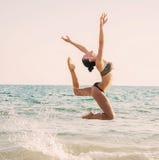 Fotografía de un bailarín de sexo femenino hermoso que salta en una playa en t imágenes de archivo libres de regalías