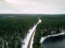 Fotografía del abejón de un camino entre el bosque en invierno Fotos de archivo libres de regalías