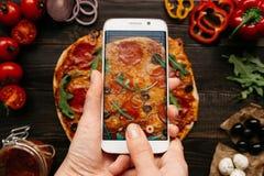 Fotografía del alimento Manos que toman la imagen de la pizza delisious con smartphone fotografía de archivo