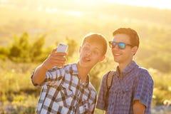 Fotografían a dos amigos felices de los individuos de los selfies lindos de la toma en el teléfono fotografía de archivo