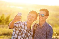 Fotografían a dos amigos felices de los individuos de los selfies lindos de la toma en el teléfono fotos de archivo