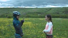 Fotografían a dos muchachas turísticas hermosas usando un smartphone en un claro de la flor Una mujer joven en un casco toma a almacen de metraje de vídeo