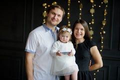 Fotografían a la familia joven en día de fiesta de la Navidad Imagen de archivo libre de regalías