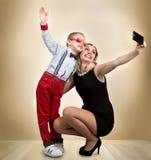 Fotografían a la madre y al hijo jovenes en un teléfono móvil, haciendo el selfie Elegante, de moda, moderno Fotos de archivo
