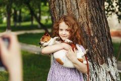 Fotografían a la niña y su perrito en el parque del verano foto de archivo libre de regalías