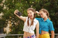 Fotografían a los mejores amigos en parque Selfie del teléfono de la foto Imagen de archivo libre de regalías