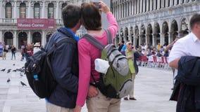 Fotografían a los turistas con las mochilas en el teléfono móvil en el cuadrado de las marcas del St almacen de video