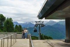 Fotografían a los turistas contra el contexto de las montañas a la estación del teleférico de la estación de esquí Imagenes de archivo