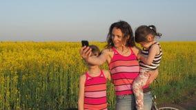 Fotografían a una madre feliz con los niños en naturaleza La familia hace a uno mismo en naturaleza Mujer con los niños en un cam metrajes