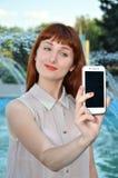 Fotografías de la muchacha en su teléfono móvil Imagen de archivo libre de regalías