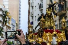 Fotografías de un hombre con su teléfono móvil la procesión de Jesús el Nazarene en Huelva, España imagenes de archivo