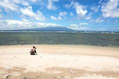 Fotograf auf tropischem Strand Stockfoto