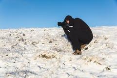 Fotograf bei der Arbeit über den Schnee im Winter Lizenzfreies Stockbild