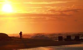 Fotograf bei Sonnenaufgang den Ozean fotografierend stockbilder