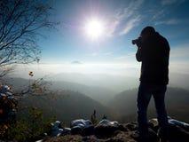 Fotograf bierze fotografie z kamerą na śnieżnym szczycie Zdjęcie Stock