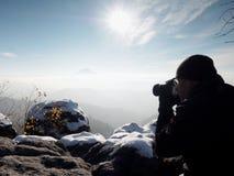 Fotograf bierze fotografie z kamerą na śnieżnym szczycie Obraz Stock