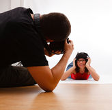 Fotograf, der das Foto des Mädchens legend auf Fußboden nimmt Stockbild
