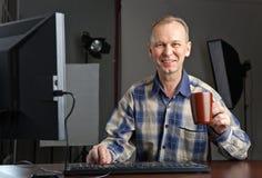 Fotograf, der an dem Computer arbeitet Stockbild