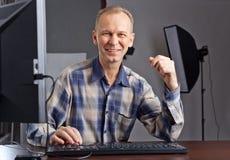 Fotograf, der an dem Computer arbeitet Stockbilder