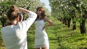 Fotograf, der die junge rothaarige Frau im blühenden Obstgarten fotografiert stock video footage