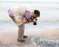 Fotograf, der ein Makro von Oberteilen auf dem Strand schießt Stockbild