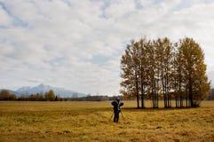 Fotograf, der eine Berufsdigitalkamera auf einem Stativ verwendet Lizenzfreie Stockbilder