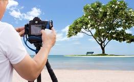 Fotograf, der Foto des Strandes mit Frangipanibaum macht Stockfotografie