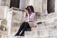 Fotograf der jungen Frau, der die Fotos sitzen auf Steintreppe macht Lizenzfreie Stockbilder