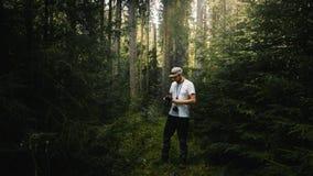 Fotograf, der Kamera in dunkelgrünem Waldlicht comin betrachtet Stockbild